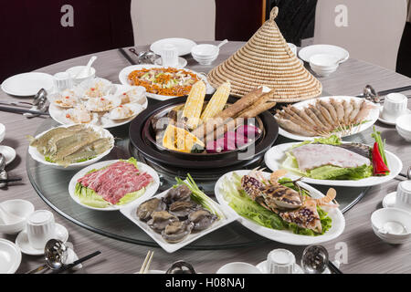 Traditional chinese tray food of seafood, produce, beef and pork on the table in restaurant - Stock Photo