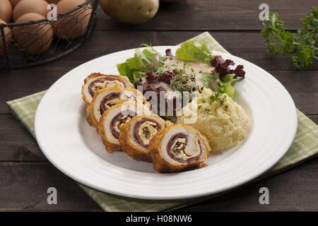 Plate of Ayam with potato and herbs on the table in restaurant - Stock Photo
