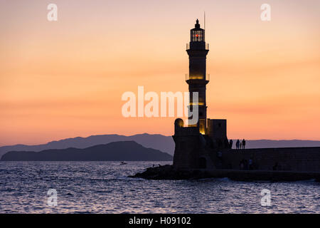 Sunset view over the Chania lighthouse at the entrance to the Venetian harbour of Chania, Crete, Greece - Stock Photo
