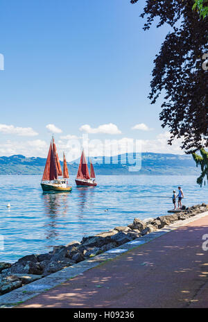 Couple fishing off the promenade of Evian as traditional sailing boats go by on Lake Geneva, Évian-les-Bains, France - Stock Photo
