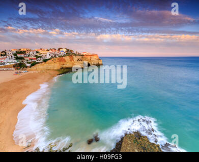 Panoramic view of Carvoeiro village surrounded by sandy beach and clear sea at sunset, Lagoa Municipality, Algarve, - Stock Photo