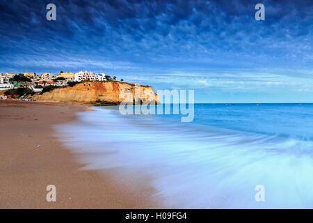 Ocean waves crashing on rocks and beach surrounding Carvoeiro village at sunset, Lagoa Municipality, Algarve, Portugal, - Stock Photo