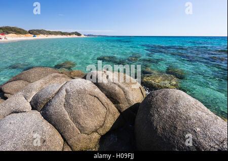 Rocks frame the turquoise water of sea around the sandy beach of Sant Elmo Castiadas, Costa Rei, Cagliari, Sardinia, - Stock Photo