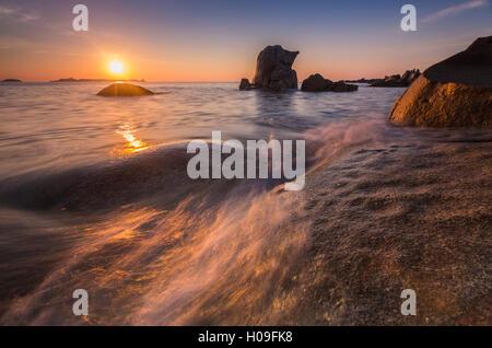Waves crashing on cliffs under the fiery sky at sunrise, Punta Molentis, Villasimius, Cagliari, Sardinia, Italy, - Stock Photo