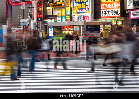 Crowds crossing a street in the Ginza district in the evening, Tokyo, Japan, Asia - Stock Photo
