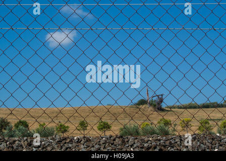 Metallic net against a sunny background with a dead tree - Stock Photo