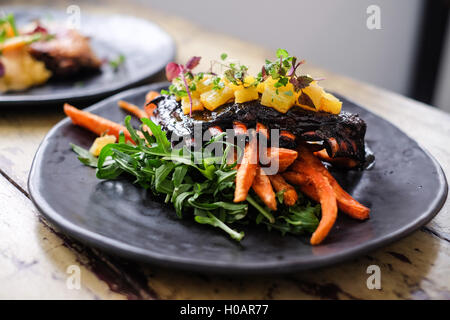 Roasted pork ribs with potato and herbs on black plate - Stock Photo