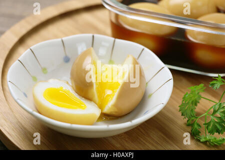 Runny eggs on white bowl with braised eggs on wooden table - Stock Photo