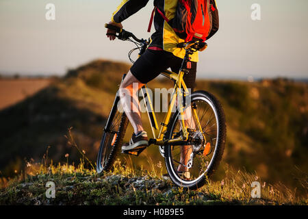 Rear View of a Sporty Man Riding a Bicycle on the Country Road. Healthy Lifestyle Concept. Toned Photo. - Stock Photo