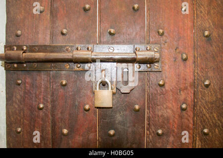 Closeup of a brass hinge and padlock on rustic wooden door with patterned bolts embedded. - Stock Photo