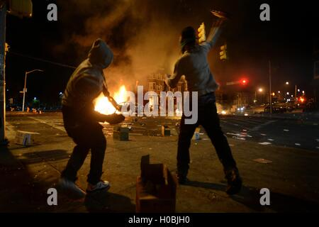 Two men throw beer bottles at burning vehicles during riots following the funeral of Freddie Gray April 27, 2015 - Stock Photo