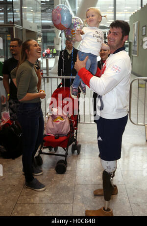 Great Britain's David Henson holding 19 month old daughter Emily alongside wife Hayley (left) as he arrives back - Stock Photo