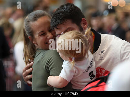 Great Britain's David Henson is greeted by 19 month old daughter Emily and wife Hayley (left) as he arrives back - Stock Photo