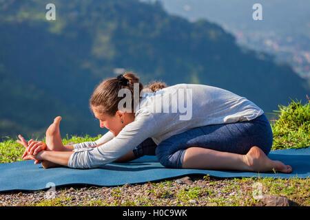 Woman in Tiryam-Mukha Eka-Pada Paschimottanasana asana stretchin - Stock Photo