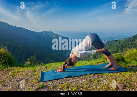 Young sporty fit woman doing yoga oudoors in mountains - Stock Photo