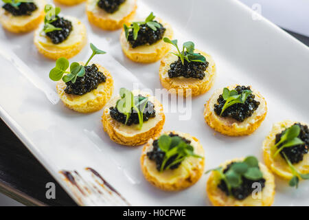 Sandwiches with black caviar on a white plate - Stock Photo
