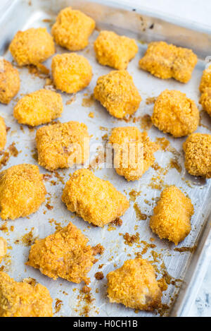 Tortilla crusted baked fish bites on plate - Stock Photo