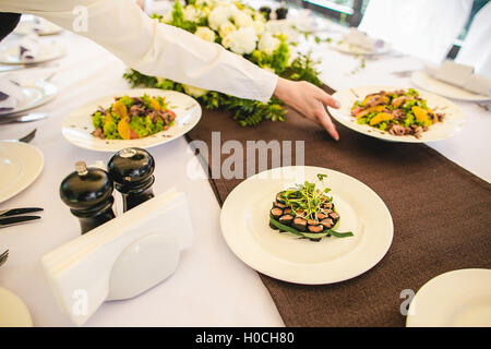 Beautifully decorated catering banquet table with different food snacks and appetizers with sandwich, caviar, fresh - Stock Photo