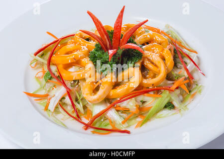 Vietnamese ring squid salad on white plate in restaurant - Stock Photo