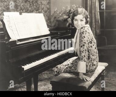 Smiling woman sitting by piano at home - Stock Photo