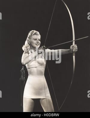 Woman in crop top and mini skirt shooting bow and arrow - Stock Photo
