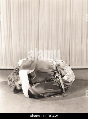 Woman curled up on floor - Stock Photo