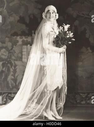 Bride carrying bouquet of lilies - Stock Photo
