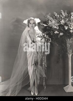 Bride standing next to tall vase of flowers - Stock Photo