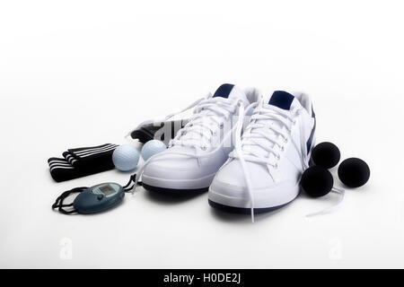 Sports shoes and various training/exercise items,including trainers, squash balls, stopwatch, golf balls, wrist - Stock Photo