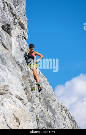 Tanned female rock climber in yellow shorts on steep rock face, with blue sky and clouds - Stock Photo
