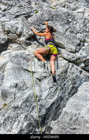 Tanned female rock climber in yellow shorts on steep rock face, with pale rock - Stock Photo