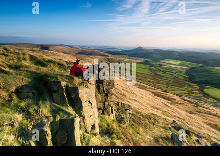 A walker sat on Shining Tor looking towards Shutlinsloe, Peak District National Park, Cheshire. - Stock Photo