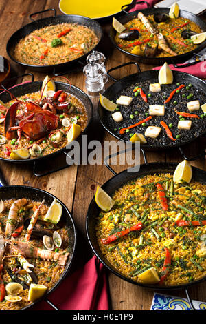 Black pans of fried lobster, mantis prawn, shrimps, clams and crabs with lemon, chili and herbs on wooden table - Stock Photo