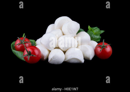 Buffalo mozzarella cheese made from milk Alibovalo on black background with tomatoes - Stock Photo