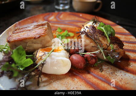 Poached eggs on the pork belly and the braised baby potatoes resting below nasturtium aioli added - Stock Photo