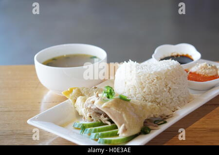 Chicken rice with sliced cucumber, bowl of soup, soyal and chili sauce on white plate - Stock Photo