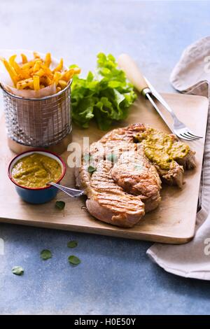 Grilled veal and chimichurri fried potato, lettuce, mashed avocado on wooden cutting board - Stock Photo