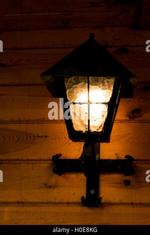 Shining, old metal lamp mounted on a wooden wall wooden building, summer evening. Vertical view. - Stock Photo