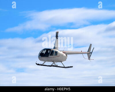 Helicopter flying in the blue sky - Stock Photo