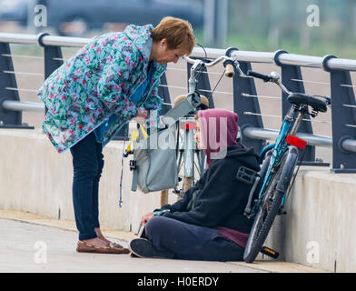 Lady helping young homeless person by giving them food. - Stock Photo
