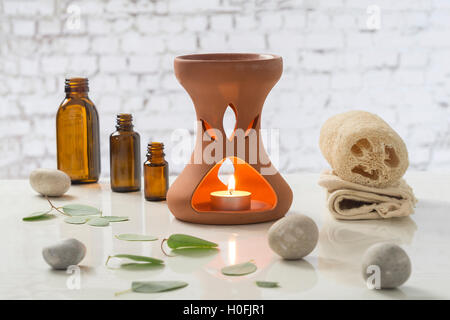 Aromatherapy votive candles burning in essential oil diffuser for wellness treatment in spa - Stock Photo