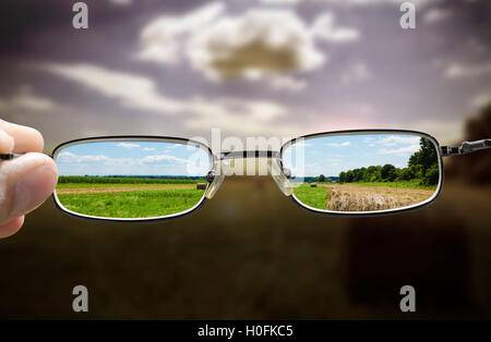 concept looking through glasses turns a gloomy day into a sunny one - Stock Photo