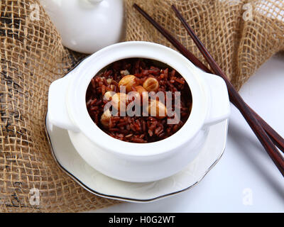 Red sticky rice with lotus bean on white bowl in restaurant - Stock Photo