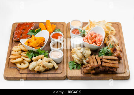 Snacks of fried shrimp, squid, tempura fish paste, potatoes and chicken on wooden cutting board - Stock Photo