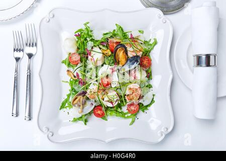 Seafood salad with clams, shrimps, squid, lettuce, tomatoes and herbs on white plate - Stock Photo