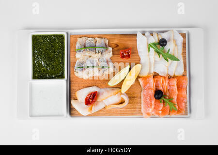 Fish plate with lemon, olive, chili and sauce on white background - Stock Photo
