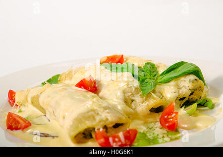 Kaneloni with bacon, chicken, cream cheese and bechamel sauce under shpiantom - Stock Photo