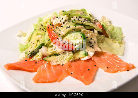 Salad with salted salmon, tomatoes and cucumbers on a green cushion with nut mix with sesame sauce - Stock Photo
