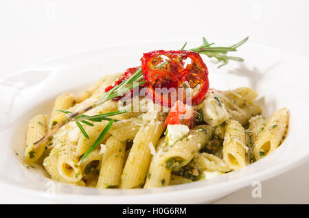Penne Pasta with cheese feta, spinach, pesto and sun-dried tomatoes - Stock Photo