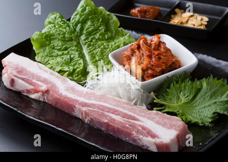 Fresh loin pork with lettuce and kimchi on black dish - Stock Photo
